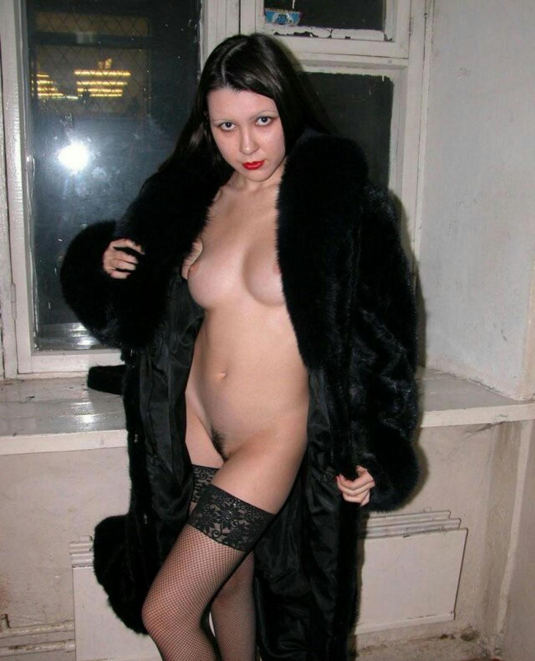Русская баба в распахнутой шубе стоит у окна с волосатой пиздой в черных чулках