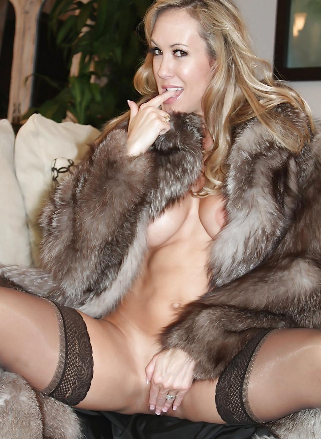 Красивая зрелая женщина блондинка в шубе на голове тело сидит на диване раздвинув ноги в черных чулках, правой рукой прикрывает интимное место, левый пальчик держит во рту