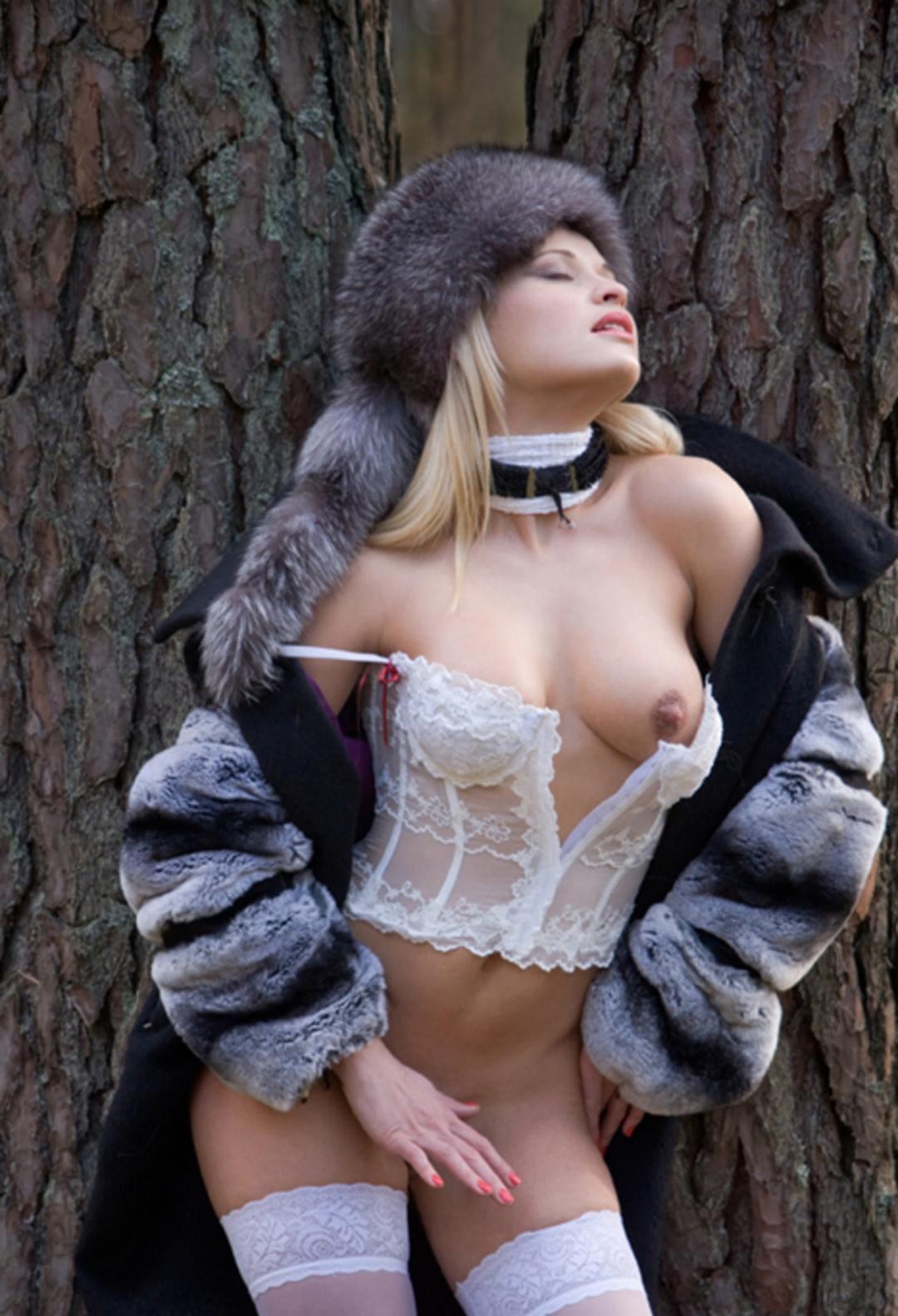 шуба на голое тело красивой блондинки распахнута открывая белый расстегнутый прозрачный корсет одна сиська открыта, на ногах белые чулки на голове пышная шапка с хвостиком чернобурки, на шее намотан шарф с ошейником