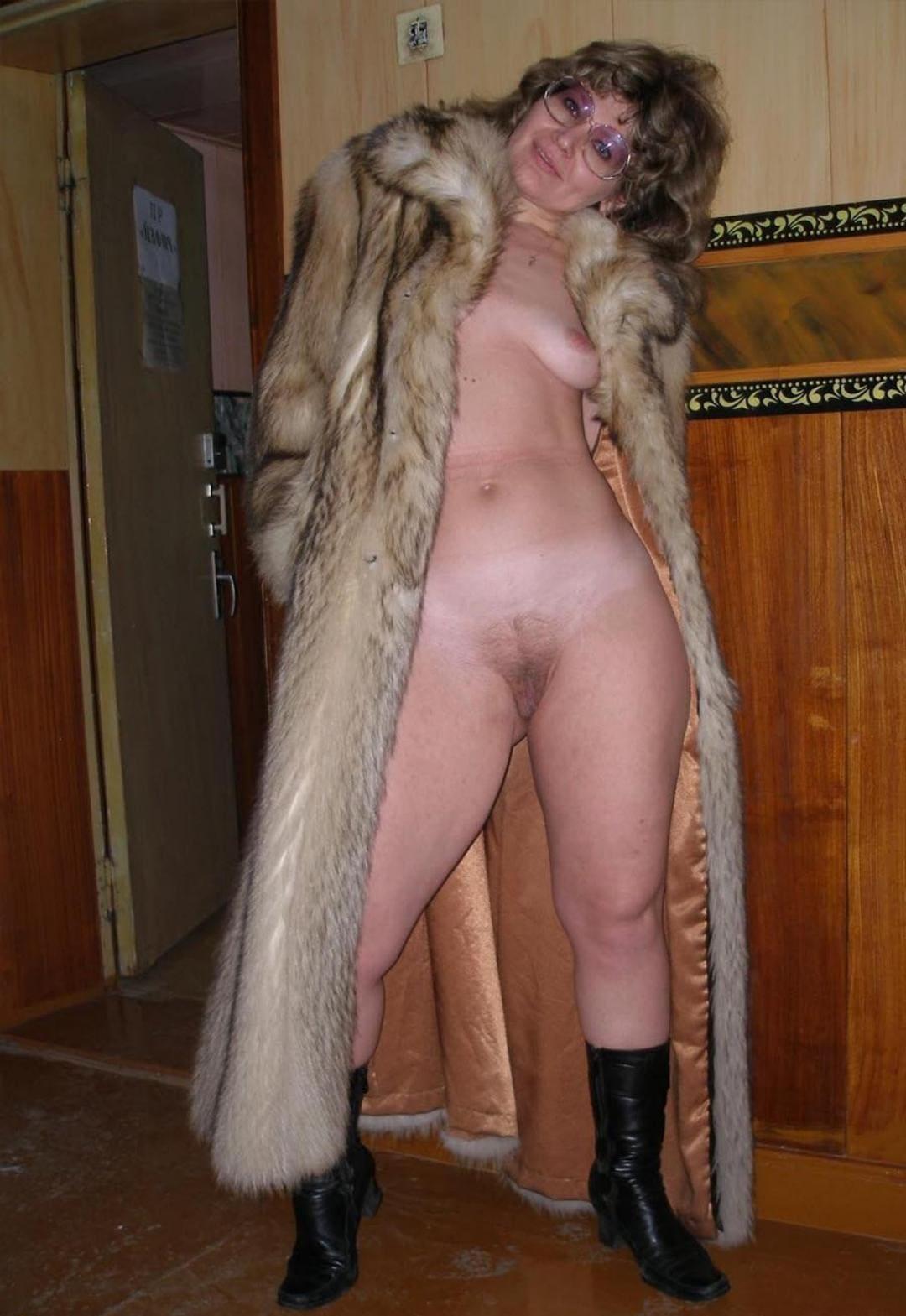 Блондинка зрелая в очках в длинной шубе на голое тело стоит в коротких черных сапожках с волосатой пиздой и маленькой грудью