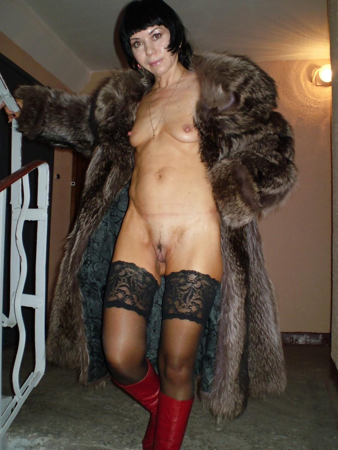 шуба длинная расстегнута на голой зрелой русской женщине брюнетке с короткой стрижкой стоит в подъезде, маленькая грудь, черные чулки, красные сапожки