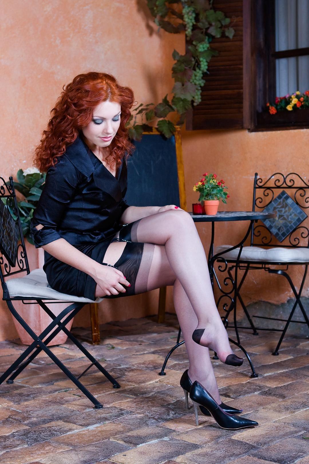 рыжая зрелая в короткой черной юбке в чулках сидит на стуле с одной ножки сняла туфельку