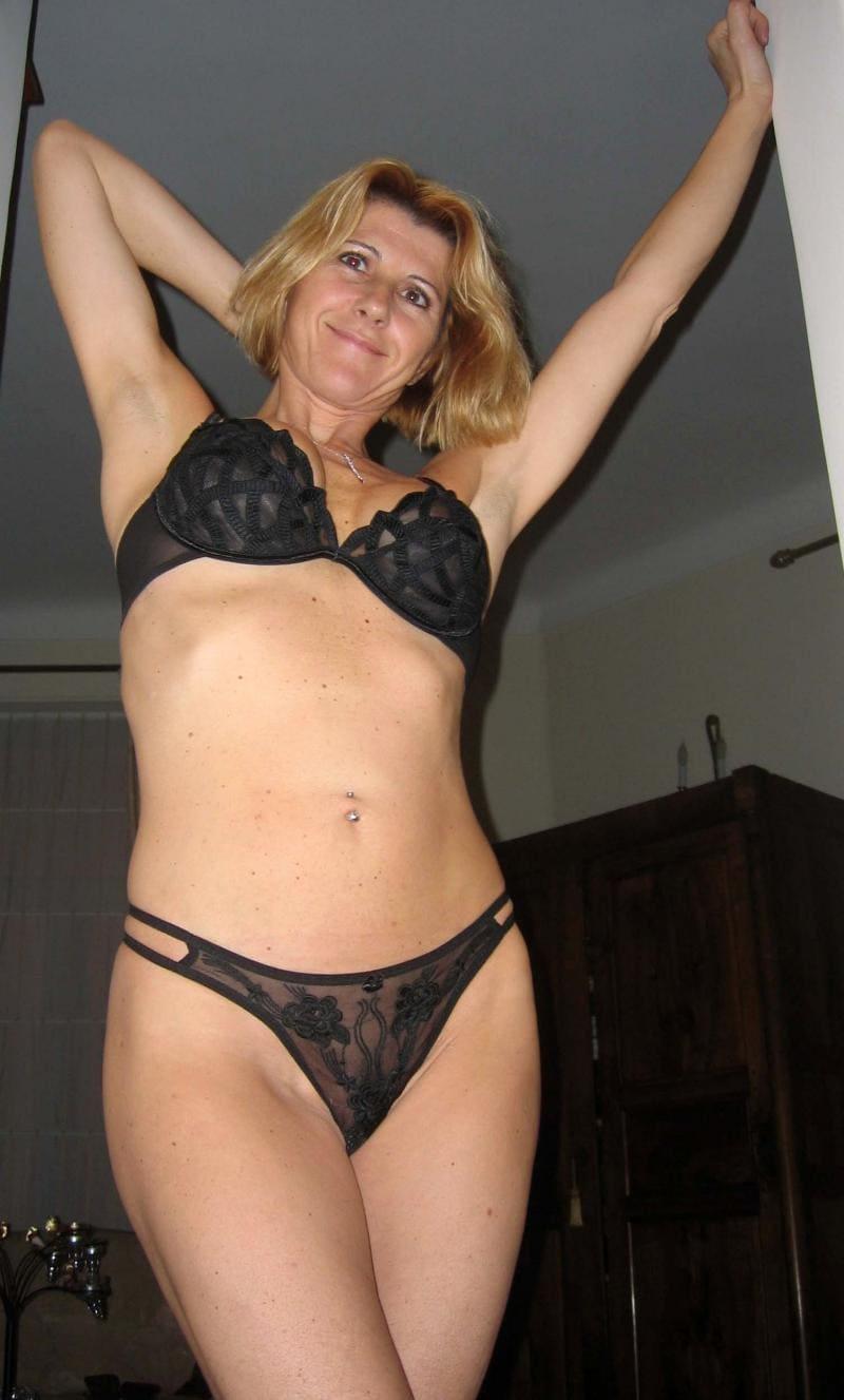 Красивая зрелая блондинка в черном нижнем белье стоит потягивается