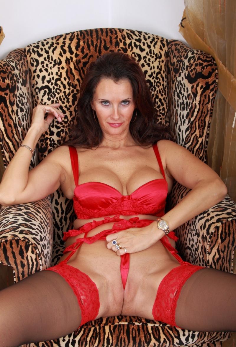 Развратная рыжая зрелая сидит в кресле в красном нижнем белье, коричневых чулках с красными подвязками, ноги широко раздвинула, трусики тянет запихнув их в пизду
