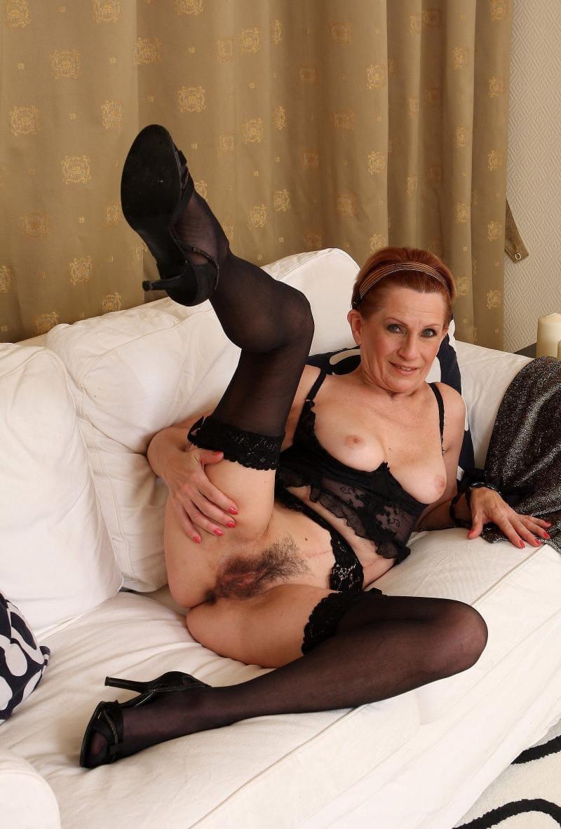 зрелые женщины в нижнем белье черном и черных колготках на белом диване блондинка с короткой стрижкой лежит на боку правую ногу подняла вверх показав очень волосатую пизду