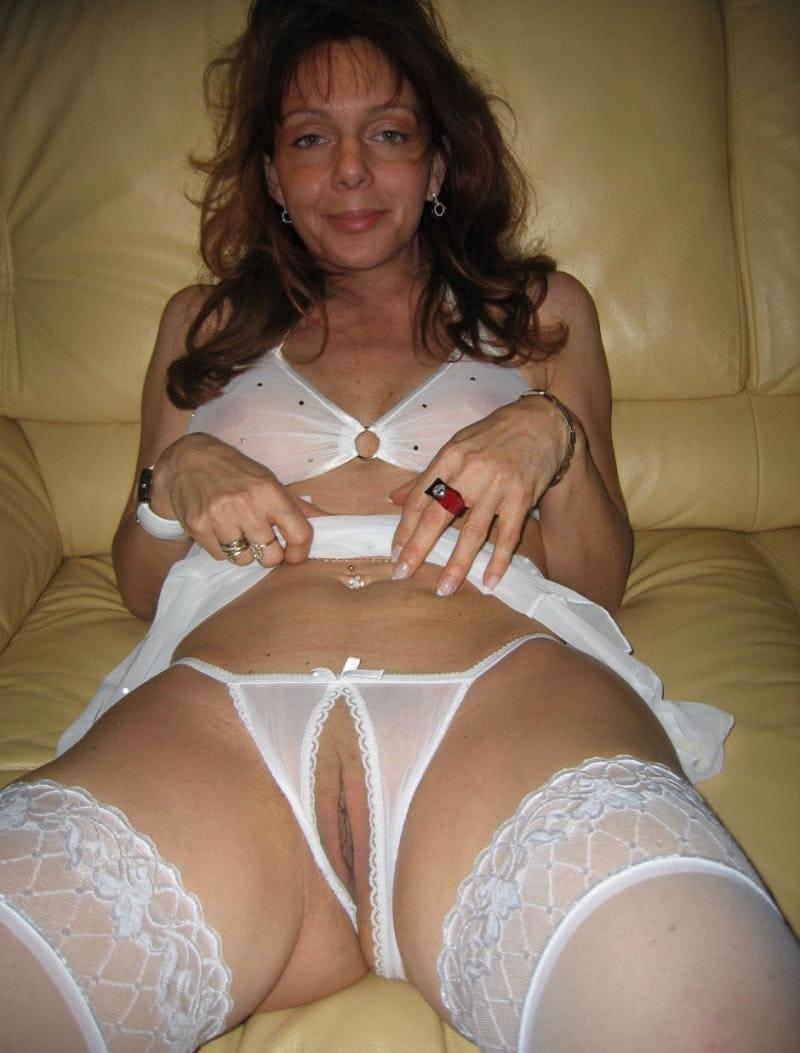 зрелые женщины в нижнем белье белого цвета и чулках на кровати лежит раздвинув ноги, в трусиках дырочка для хуя