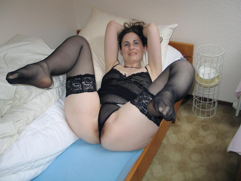 женщины в нижнем белье домашнее на кровати лежит раздвинула и согнула в коленях ноги в чулках