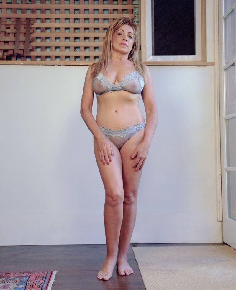 Блондинка зрелая босая стоит в светлом просвещающемся нижнем белье