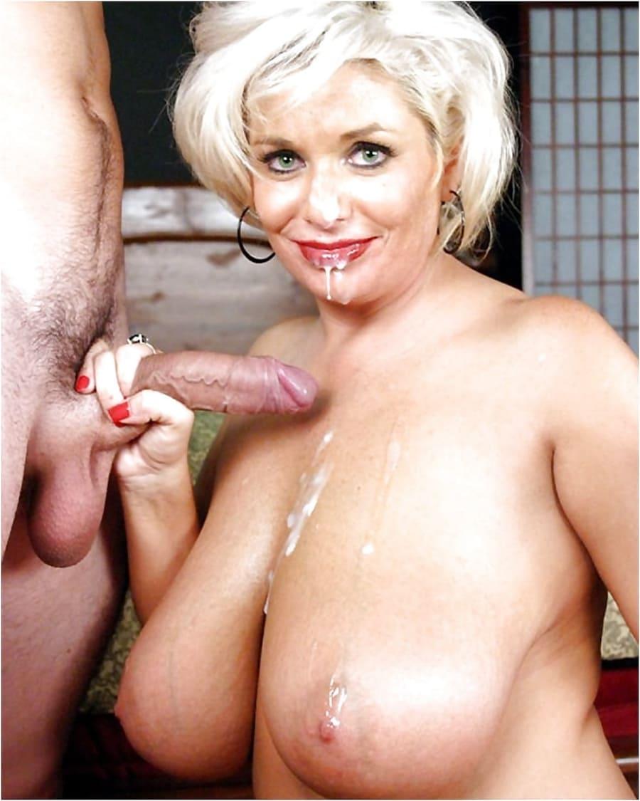Зрелая голая блондинка с большими сиськами стоит на коленях в правой руке держит длинный член, который обкончал ей губы подбородок и белая густая сперма стекает по сиськам