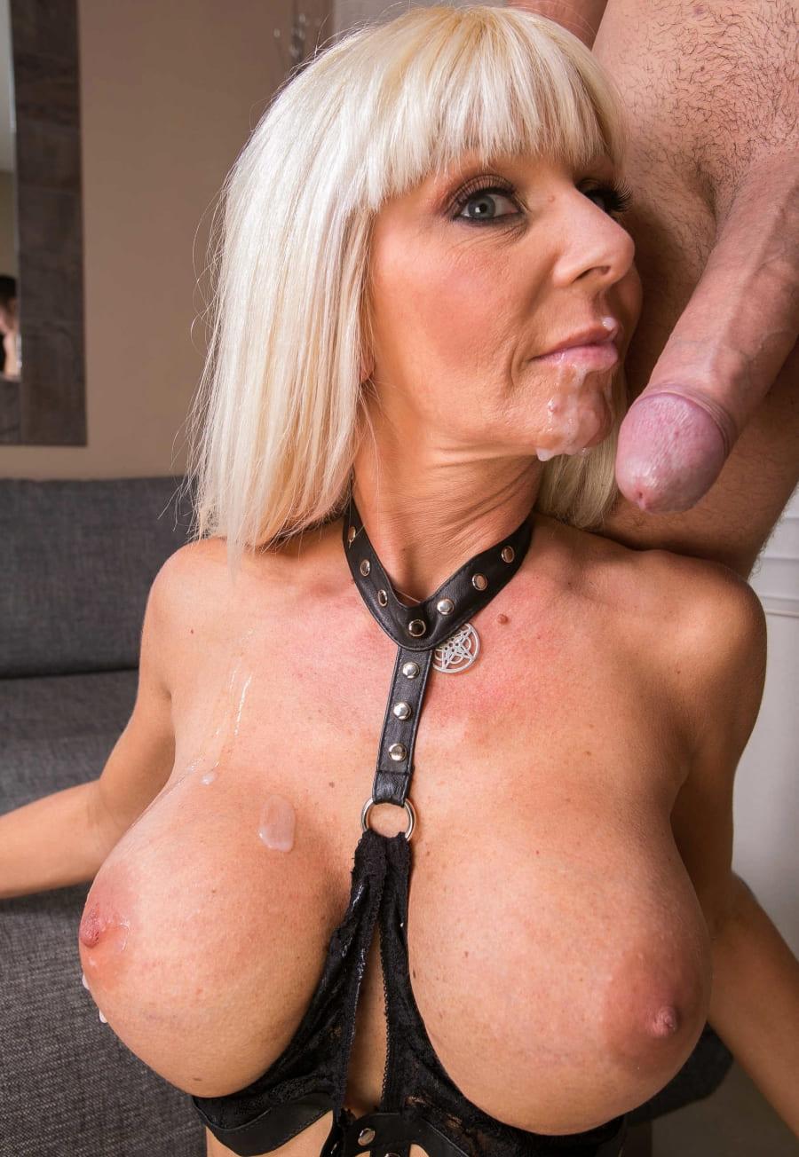 сперма на лицо зрелой блондинки с ярко накрашенными глазами, прямым волосом, одета в кожаный костюм для БДСМ