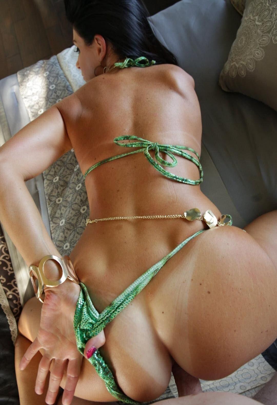 Жгучая брюнетка с красивой фигурой раком в сексуальном салатовом купальнике и стрингах стоит рукой оттягивает трусики освобождая место для члена