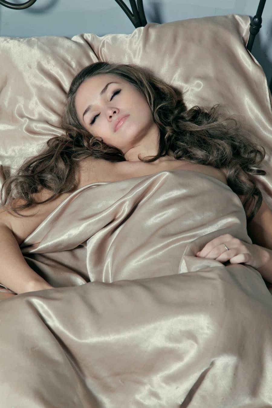 Спящая красивая голая девушка с длинным шикарным волосом сладко спит на кровати немного укрыта атласным покрывалом