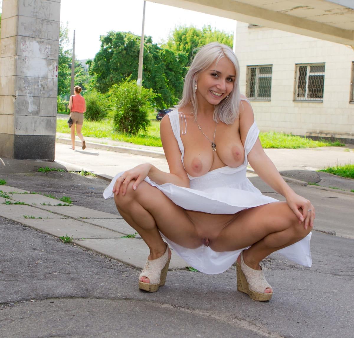 эксбиционистка блондинка сидит вприсядку раздвинув ноги без трусов и сняв плечики белого платья оголила большую грудь, босоножки на платформе и каблуке