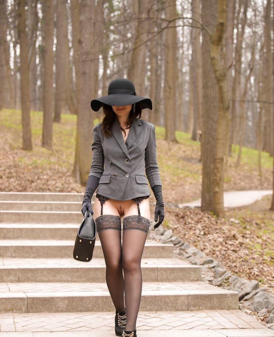 Идет в парке дама брюнетка в черной шляпе с широкими полями закрывающими лицо, в сером пиджаке чулки на поясе без трусиков в туфлях на каблуке, черные длинные перчатки на руках