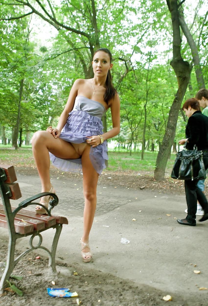 В парке девушка задрала платье ногу поставила на лавочку задрала подол платья показав, что она без трусиков