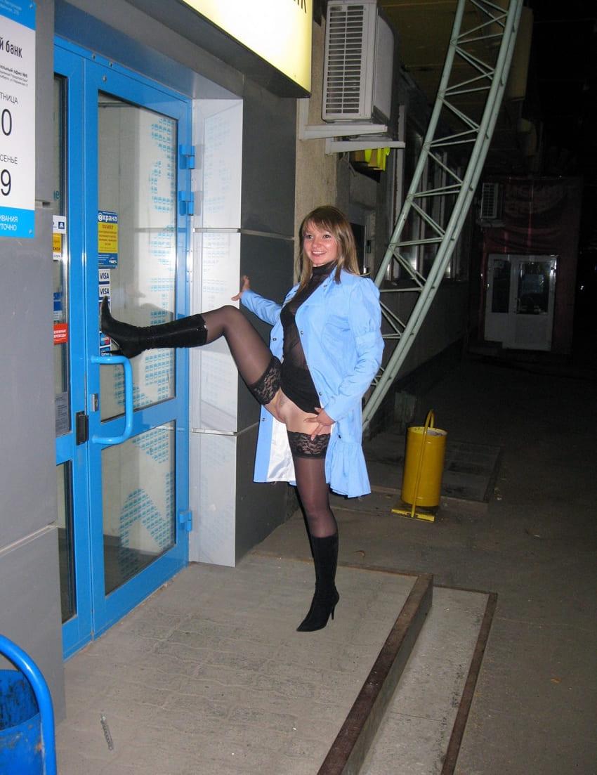 русские эксгибиционистка стоит задрав ногу в чулках на дверь банка в черных чулках распахнутом голубом пальто без трусов