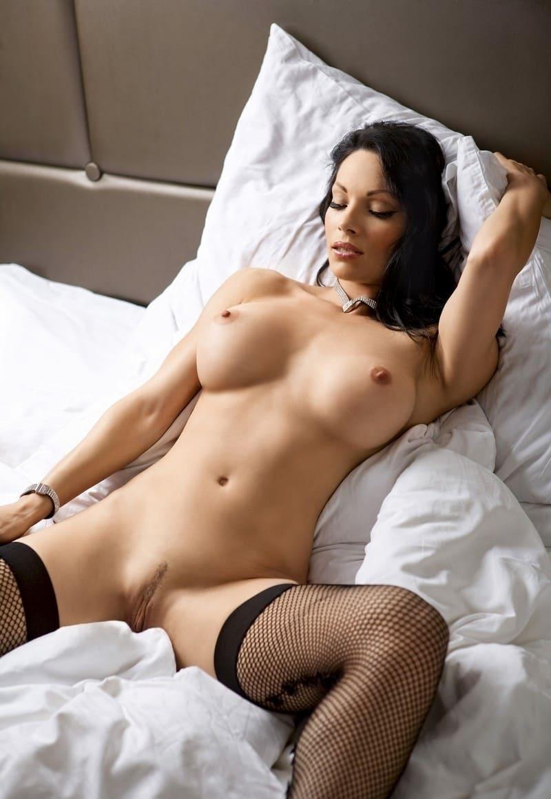 красивые девушки голые фото эротики брюнетка на спине на белых простынях лежит раздвинув ноги в черных в сетку чулках