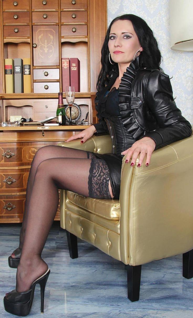 фото зрелой брюнетки в черных чулках короткой юбке сидит в кресле показывает свои красивые ножки в босоножках на высоком каблуке и платформе