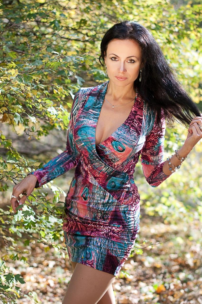 фото зрелой брюнетки в коротком цветном платье с глубоким декольте и большими сиськами на улице стоит