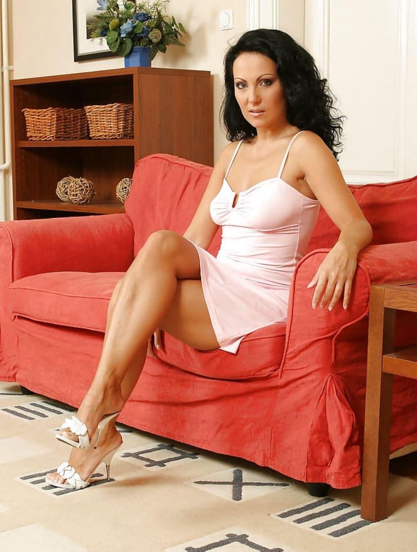 фото красивой зрелой брюнетки с длинным волосом сидит на красном диване в коротком белом пеньюаре и открытых босоножках показывая красивые ножки