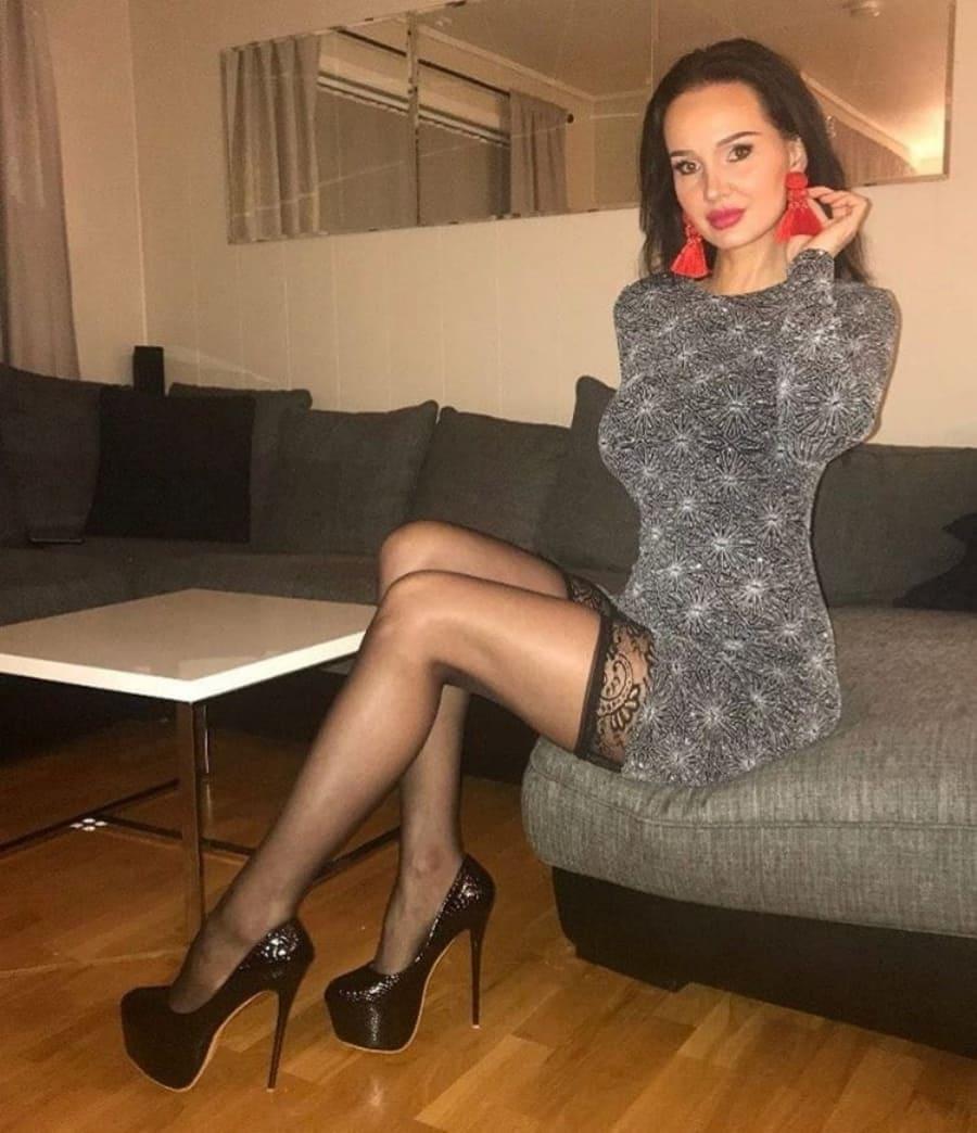 фото зрелой брюнетки на диване в коротком платье в чулках на каблуках
