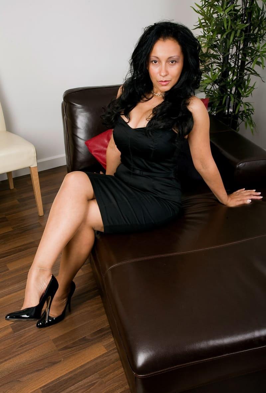 фото зрелой брюнетки в черном платье сидит на диване в туфлях на каблуках, глубокое декольте, большие сиськи, ножка закинута на ножку, длинные волосы распустила, строит глазки