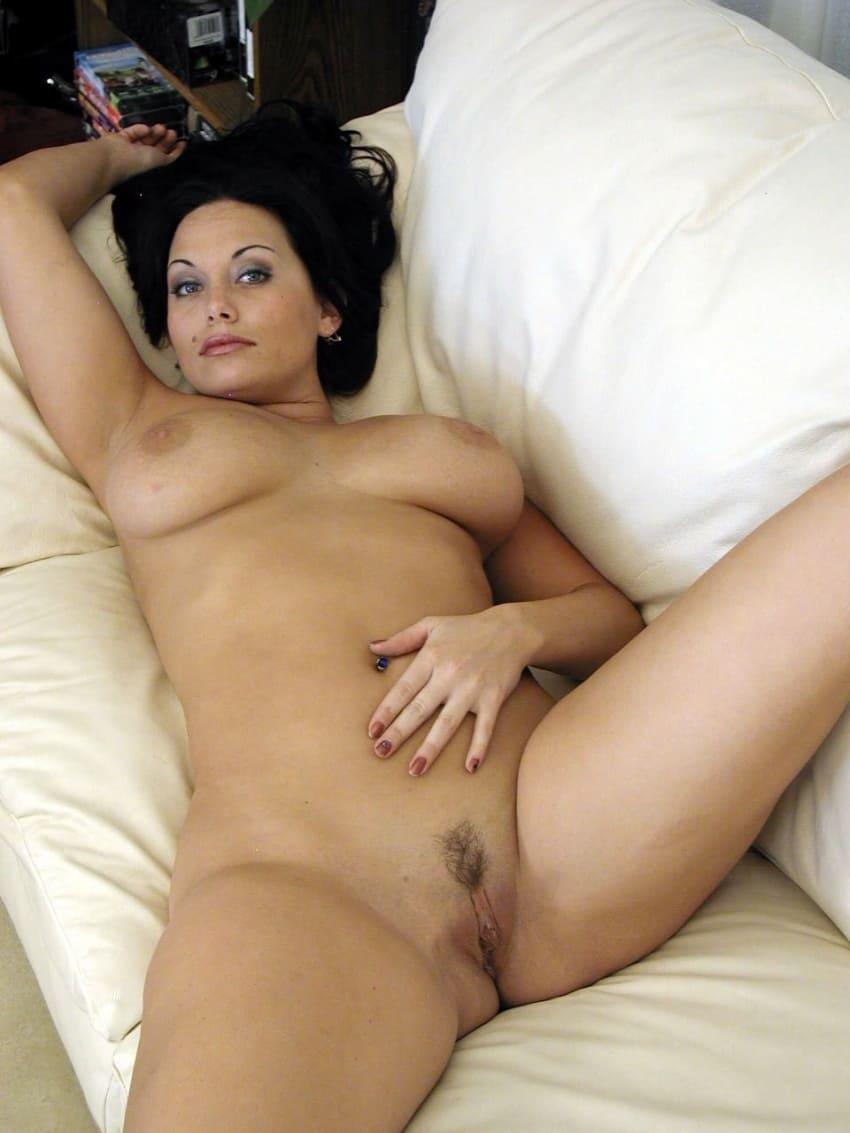 фото красивой голой зрелой брюнетки лежит на спине на кровати широко раздвинула ноги, интимная стрижка, большие сиськи