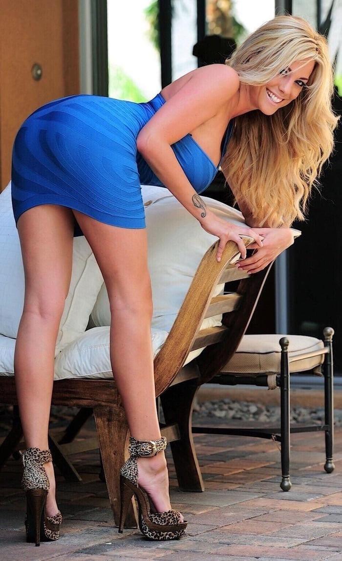 красивые блондинки раком уперлась на поручень деревянного ложе, длинные распущенные волосы в коротком голубом платье с большим декольте и сиськами, стройные ножки, леопардовые босоножки с пряжкой на высоком каблуке и платформе стоит улыбается