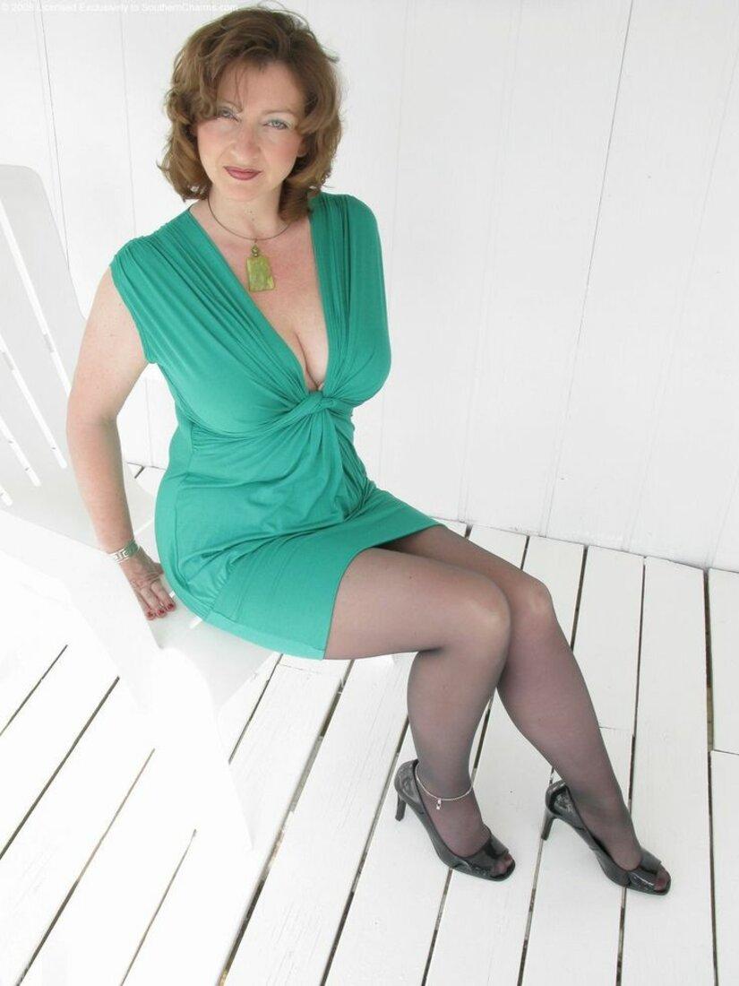 фото зрелых дам в зеленом платье с большим декольте колготках и туфлях