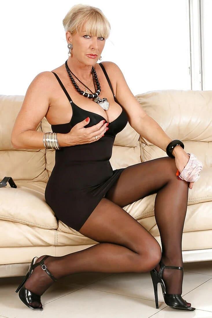 фото зрелых дам блондинка в нижнем белье и черных чулках на каблуках сидит на диване держится одной рукой за сиську