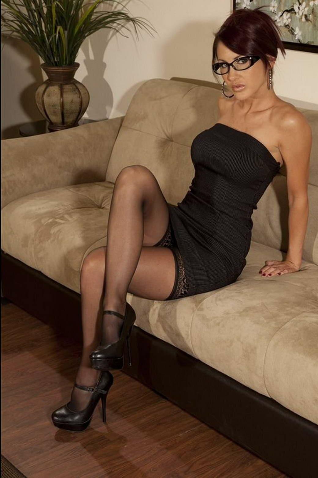 красивые мамки сексуальные фото в очках на диване в чулках и коротком черном вечернем платье сидит нога на ногу закинута, туфли на высоком каблуке с пряжкой