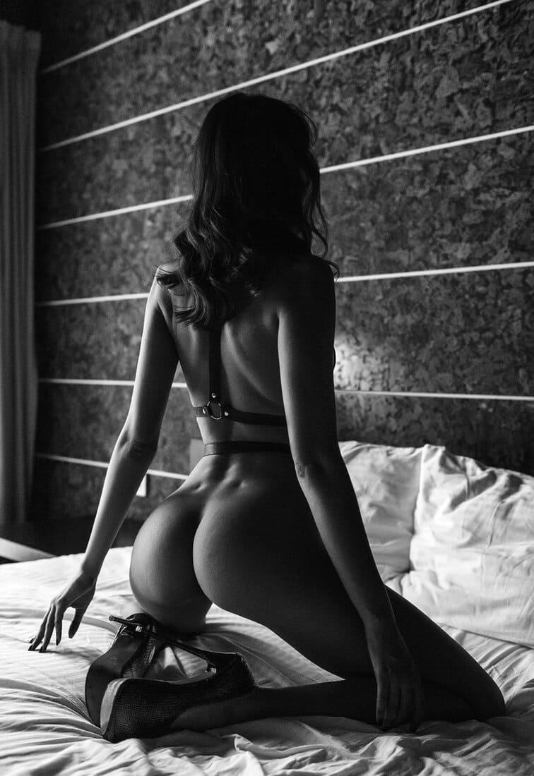 черно белое фото девушки спиной стоит на кровати на коленях на каблуках